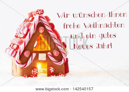 Gingerbread House In Snowy Scenery As Christmas Decoration With White Background. Candlelight For Romantic Atmosphere. German Text Frohe Weihnachten Und Ein Gutes Neues Jahr Means Merry Christmas And Happy New Year