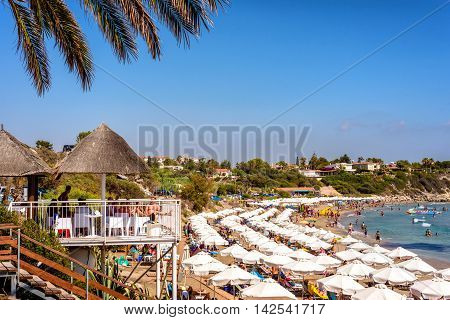 PAPHOS CYPRUS - JULY 24 2016: People resting at the Coral Bay Beach on bright summer day.
