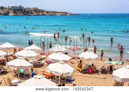 PAPHOS CYPRUS - JULY 24 2016: Tourists and locals enjoying a nice summer day at the Coral Bay Beach.