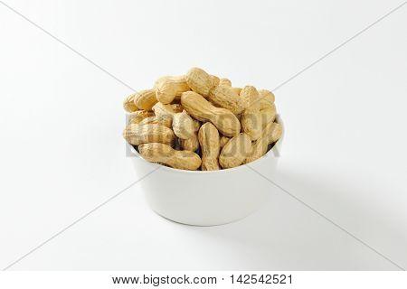 Bowl of raw unshelled peanuts