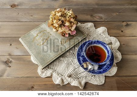 Reminiscing with a cup of tea in antique blue and white china cup and saucer with Memory Lane photograph album and faded hydrangea flower head on wooden table