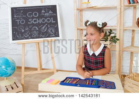 Portrait of lovely girl drawing in copybook at lesson . concept of education and children's knowledge