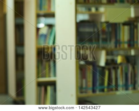 blurred image of a public library showing bookshelves and books