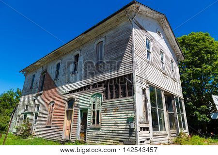 Mainesburg PA - July 26 2016: An old weathered and aging white store and residential building no longer in use on Route 6.7
