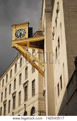 Impressive gold clock on the side of a building