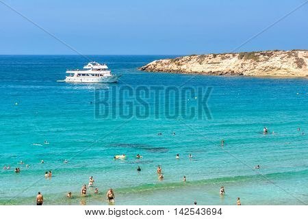 PAPHOS CYPRUS - JULY 24 2016: Recreational boat with tourists at Coral Bay Beach.