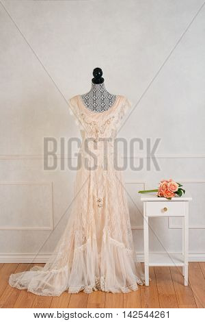 vintage wedding dress with rose bouquet on table