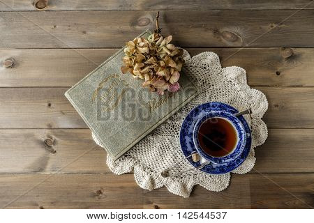 Top down image of antique blue and white china cup and saucer of black tea on lace cloth alongside old Memory Lane photograph album and faded hydrangea flower head