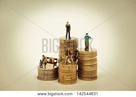 People of various social groups on pile of coins.
