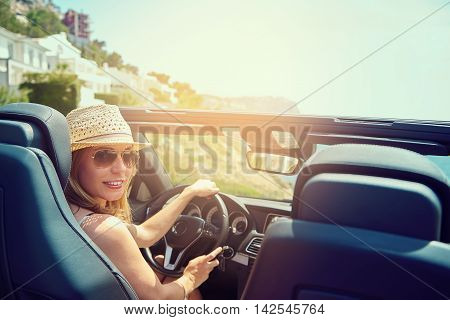 Beautiful young woman with hat and sunglasses in convertible top automobile looking back toward passenger seats