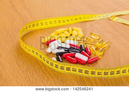 Colorful tablets and centimeter. Dietary pills. Beautiful body.