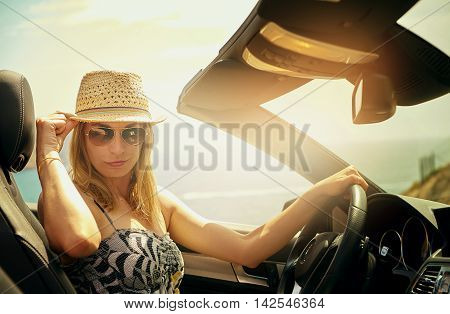 Smirking young woman in sunglasses holding the brim of her straw hat while driving her luxury retractable roof automobile in bright sunlight