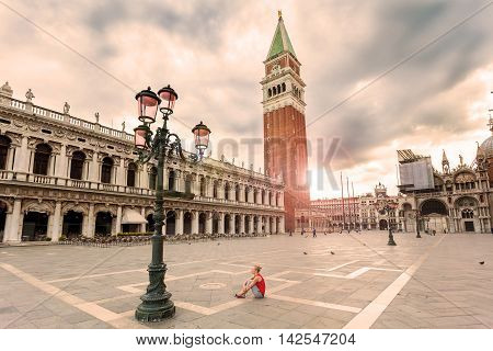 Girl female traveler sitting on the Piazza San Marco in Venice at sunrise and enjoy the area without people. The main square of the old town. Italy.