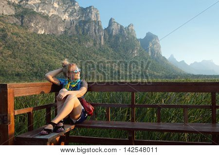 portrait of young beautiful girl is watching sunset in summer environment