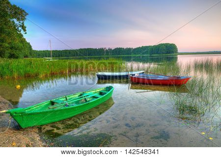Rowing boats floating over the Lake Lasmiady waters early morning. HDR image. Masuria Poland.