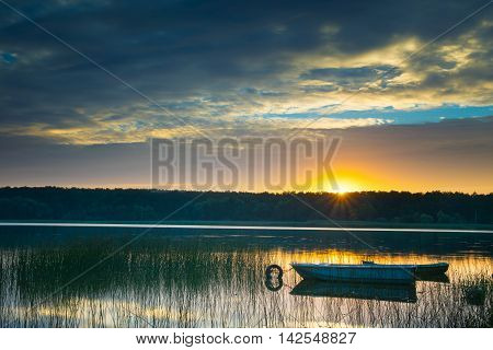 Rowing boats floating over the Lake Lasmiady waters. The sun rises just behind them. Masuria Poland.
