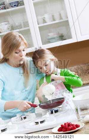 view of young beautiful girl cooking at the kitchen with her mama