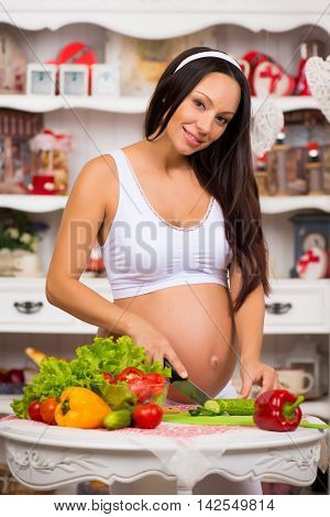 Healthy nutrition and pregnancy. Young smiling pregnant woman cuts vegetables on salad