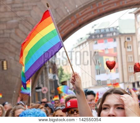 STOCKHOLM SWEDEN - JUL 30 2016: Hand holding the colorful rainbow pride flag in the Pride parade July 30 2016 in Stockholm Sweden
