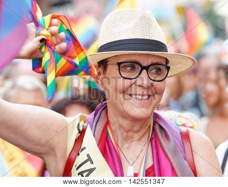 STOCKHOLM SWEDEN - JUL 30 2016: Senior smiling woman holding a rainbow flag colorful background in the Pride parade July 30 2016 in Stockholm Sweden