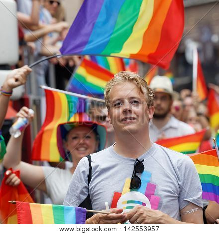 STOCKHOLM SWEDEN - JUL 30 2016: Smiling blonde man lots of rainbow Pride flags in the background in the Pride parade July 30 2016 in Stockholm Sweden