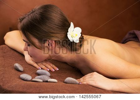 Woman in spa salon with orchid flower in her hair