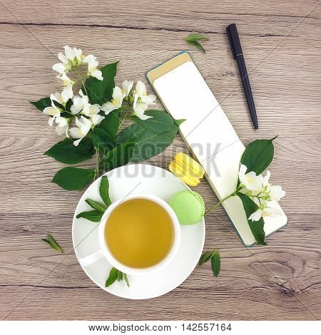 Spring bright composition of cup of green tea macarons notebook with a pen and jasmine flowers on wooden table. Flat lay top view