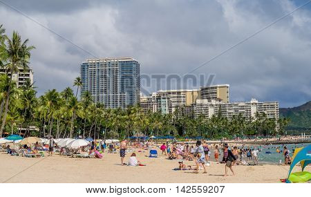 HONOLULU, USA - AUG 7: Sun lovers on Waikiki beach on August 7, 2016 in Honolulu, Usa. Waikiki beach is neighborhood of Honolulu, best known for white sand and surfing.