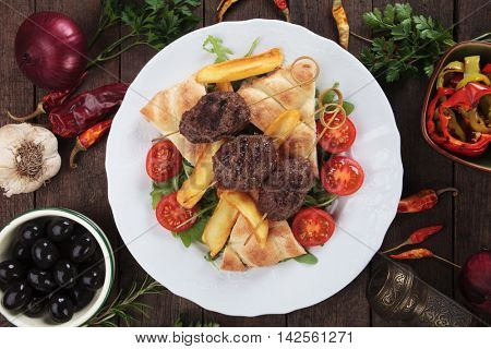 Kofta kebab, oriental minced meat skewer with pita bread and french fries
