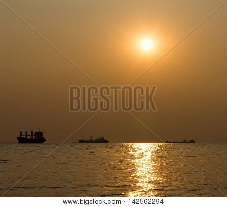 Silhouettes of ships in the sea against the sunset. shallow depth of field