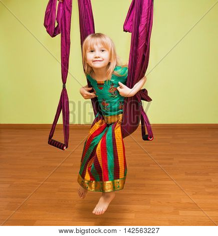 Little girl making aerial yoga exercises, indoor, fly yoga