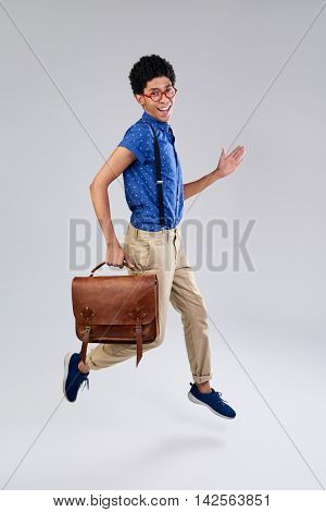 mixed race young man dressed as nerd geek jumping in mid air, movement isolated in studio