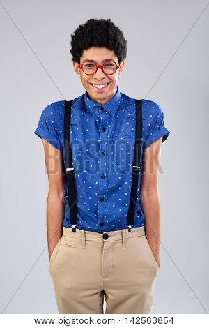 Smiling mixed race guy with afro smiling dressed as studious geek different fashion sense