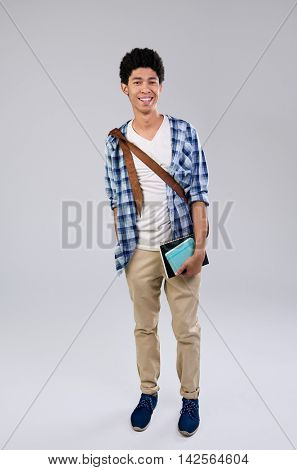 Happy mixed race male student holding books and messenger bag isolated on grey background