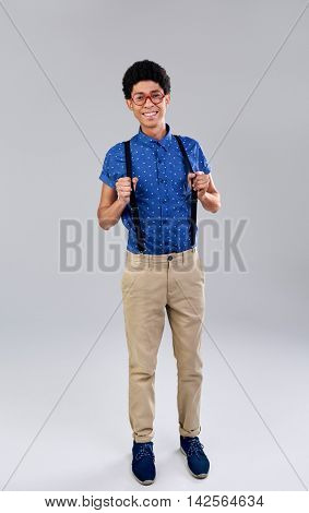 Confident portrait of nerd geek studious young man with suspenders and glasses spectacles