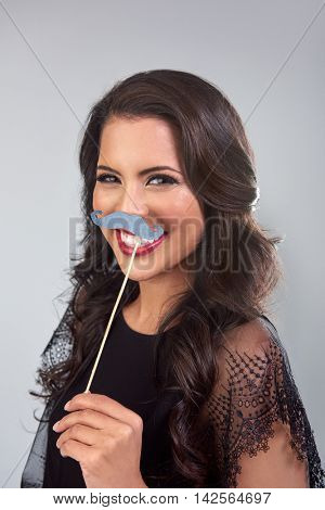 Pretty glamorous woman posing with photobooth props fake mustache