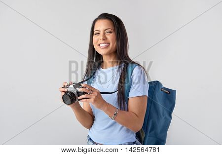 Happy tourist woman holding a vintage camera in studio, isolated on grey
