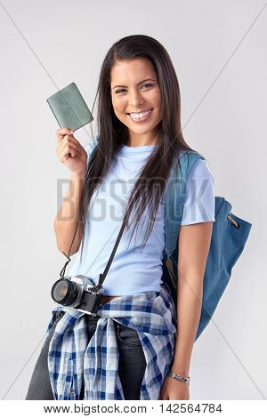 Happy tourist woman holding passport in studio, isolated on grey