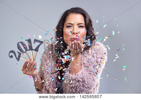 Pretty glamourous woman welcoming the new year 2017 blowing confetti into camera, photobooth style image