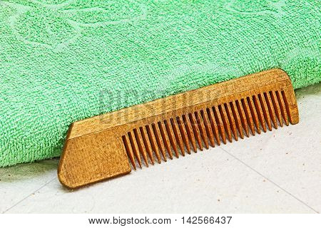 Wooden Hair Comb and Green Towel on White Cloth.Taken Closeup.