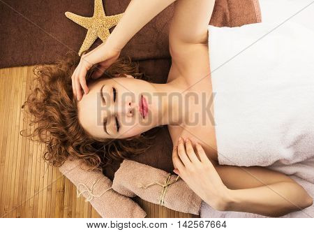 Lying relaxing beautiful woman with starfish spa