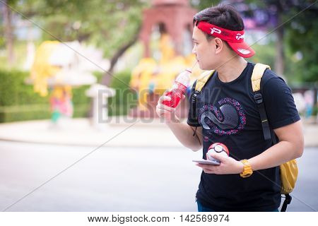 BANGKOK THAILAND – August 142016: Trainer boy playing pokemon pokemon ball And are wondering why pokemonstop in a drinking water well Lighting with sun flare