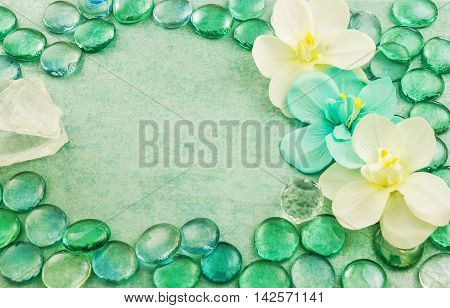 Macro view of green glass drops with white flowers orchid and bar of sea salt aqua background