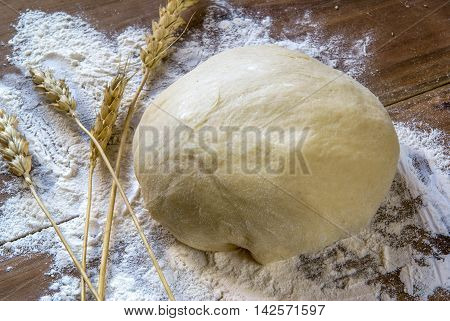 The finished raw dough on a wooden table, spikelets of wheat