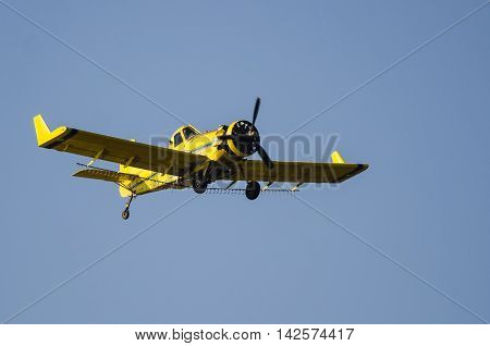 Yellow Crop Dusting Plane Flying in a Blue Sky