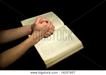 A mans hands clasped in prayer over a  Bible