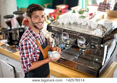 Satisfied male waiter holding cup hot coffee