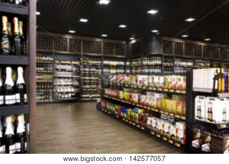 Wine shelves in supermarket out of focus unrecognizable.