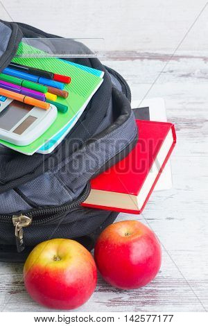 School backpack with supplies and two apples on white desktop close up