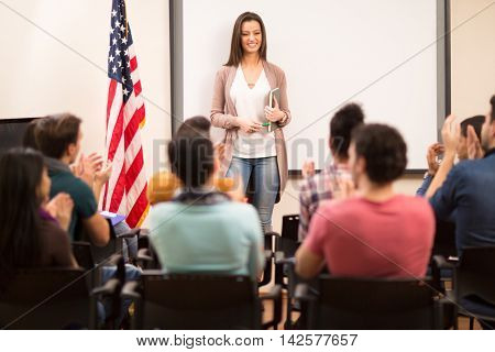 Satisfied assistant finished teaching and her students clapping hands